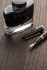 木目の背景に万年筆とインクのアップ