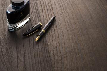 木目の背景に万年筆とインク