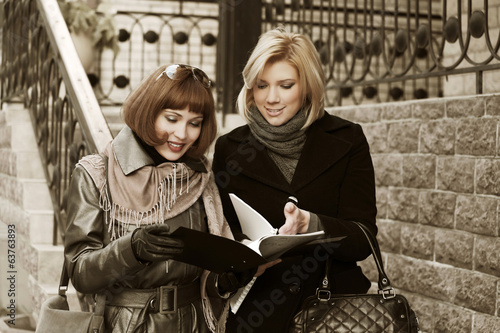 Two young business women with financial folder