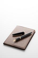 白背景に万年筆と手帳