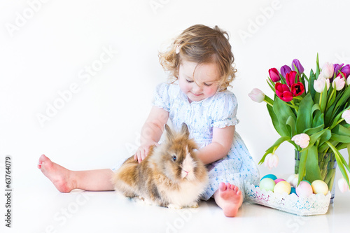 Cute toddler girl with a bunny on Easter next basket with eggs