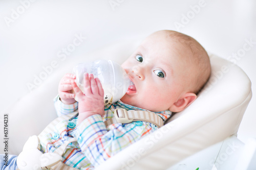 Adorable little boy sitting in a high chair drinking milk
