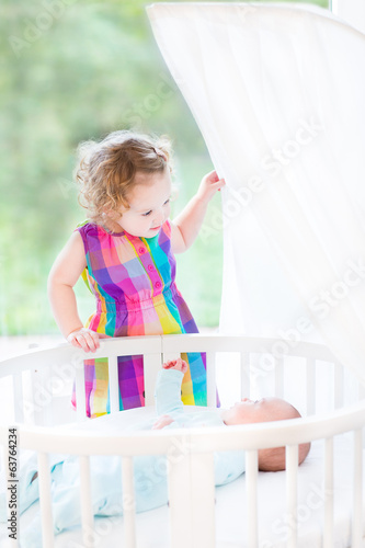 Cute laughing toddler girl playing with her newborn baby brother