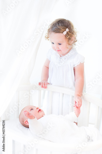 Beautiful toddler girl wearing white dress wih her brother