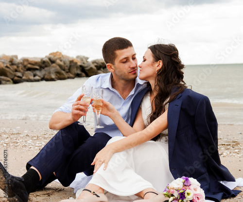 Loving bride and groom sitting on the seashore.