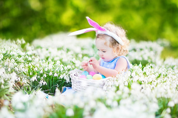 Adorable toddler girl wearing bunny ears with Easter eggs