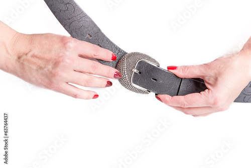 female hands holding a belt with a buckle