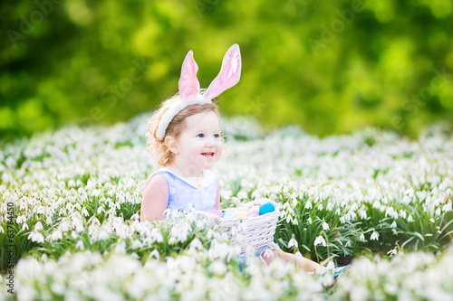 Beautiful toddler girl in bunny ears and blue dress on meadow