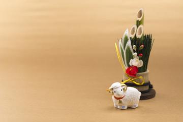 金色の背景に門松と羊の干支置物