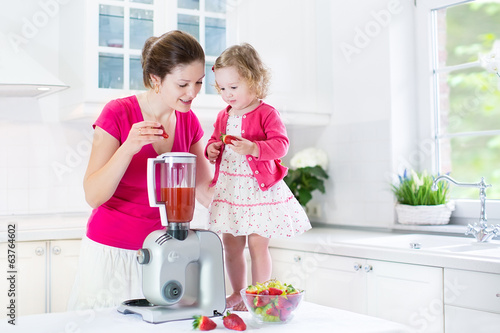 Happy laughing toddler girl and her mother making fresh juice