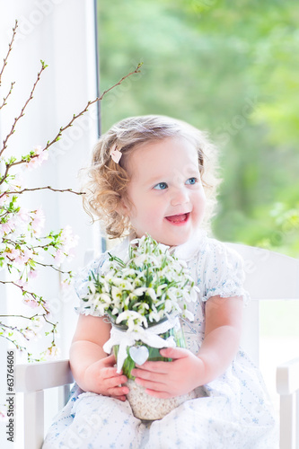 Portrait of curly toddler girl in a white dress next big window