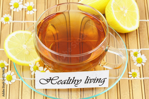 Healthy living card with cup of tea, chamomile flowers and lemon