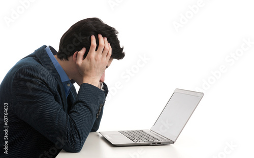 stressed man looking at his laptop computer with his head in his