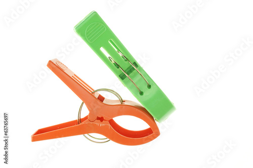 Big green and orange clothes pegs isolated