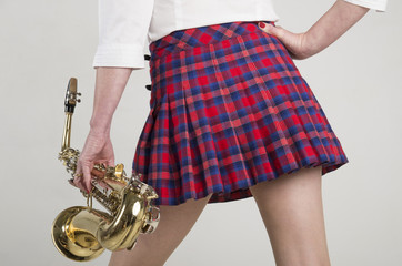 Woman in short skirt carrying a Saxophone
