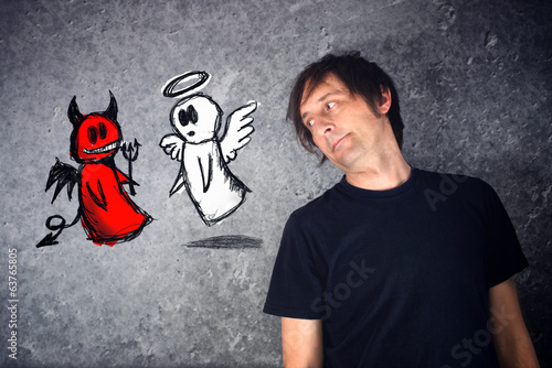 Casual man looking at doodle drawing of angel and devil fighting
