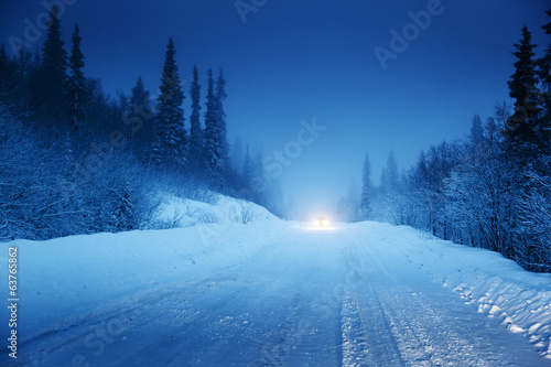 lights of car and winter road in forest