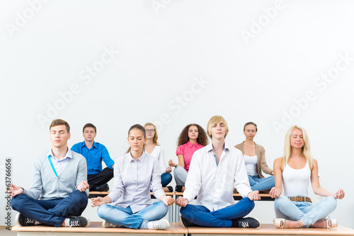 group of young people meditating
