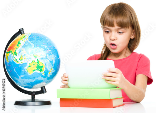 Young girl is using tablet while studying