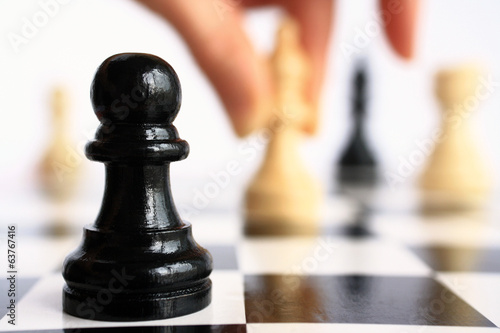 Human hand moves a chess piece on a  pawn background closeup.