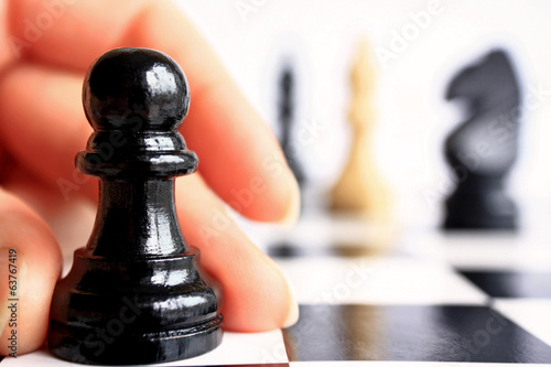 Human hand moves a chess piece pawn on the chessboard macro.