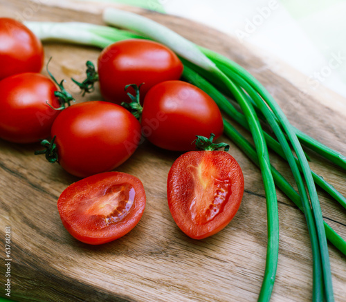 red tomatoes and green onions on the cutting board