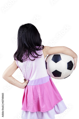 Back view of little girl holding a ball