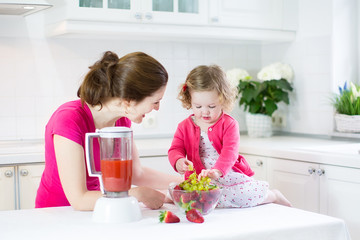 Laughing toddler girl and beautiful mother making breakfast