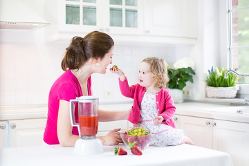 Mother with her toddler girl making fresh juice for breakfast