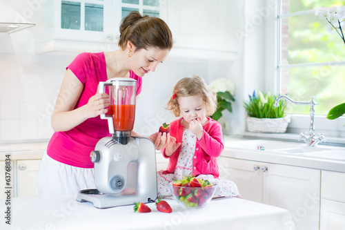 Toddler girl with her beautiful young mother making fresh juice