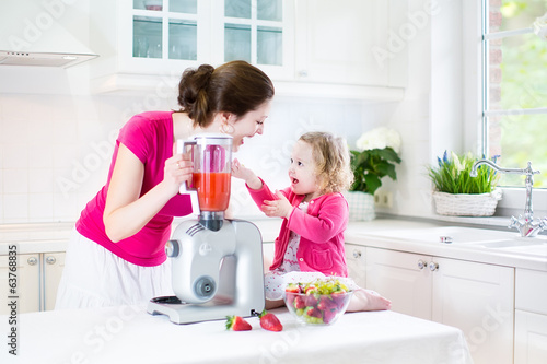 Young mother with her laughing toddler girl cooking breakfast