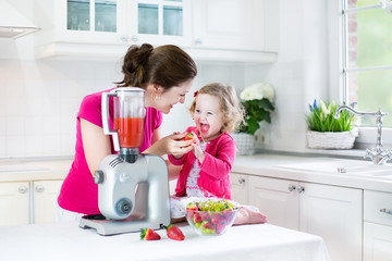 Funny toddler girl and her young mother makin breakfast