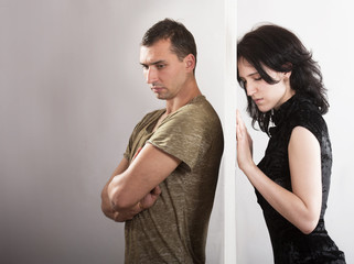Conflict between man and woman standing on either side of a door