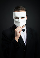 Man holding a mask in front of his face, dark background