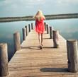 elegante Frau läuft auf einen Steg am See