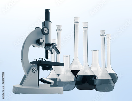Laboratory metal microscope and test tubes with liquid toning in