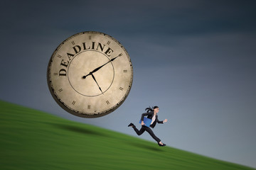 Businesswoman running with big deadline clock