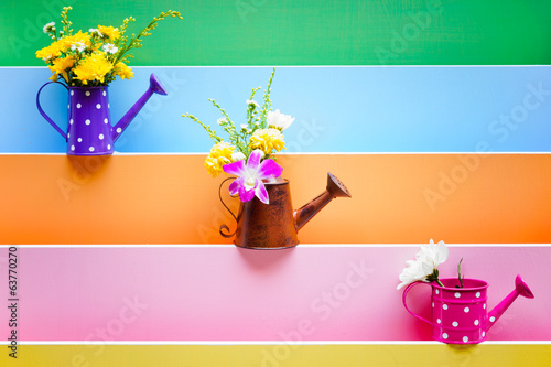 colorful wood texture with watering cans decorated with flowers