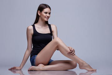 Young beautiful woman sitting and posing in the studio