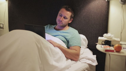 Happy man lying on bed and using tablet