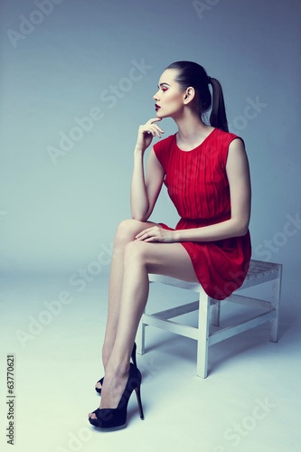 young elegant woman in red dress sit on stool, studio shot