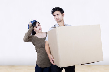 Confused couple bring box at new home