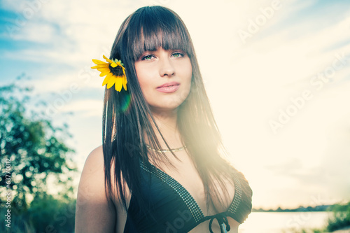 Pretty women against sky with sunflower in her hair