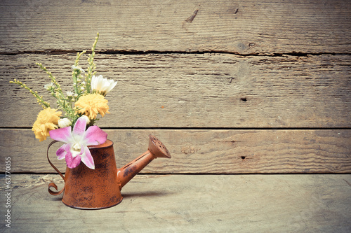 wood texture with old rusty watering cans with flowers