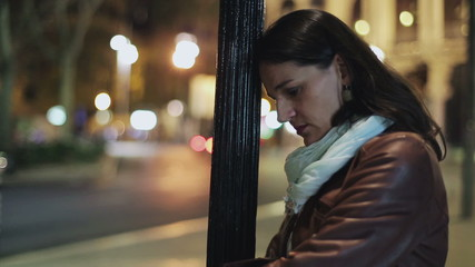 Sad woman standing alone on the street at night