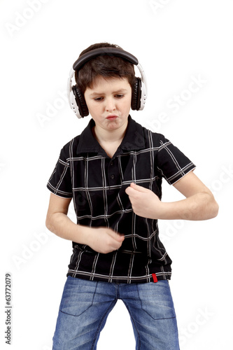 Portrait of a happy young boy listening to music and dancing