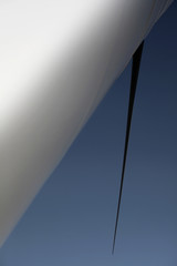 An abstract view at tower and wing below the huge wind turbine