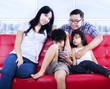 Happy family relaxing on red sofa at apartment