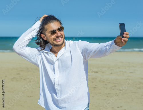 man takes a self portrait on the beach
