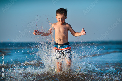 Little boy running through water at the beach